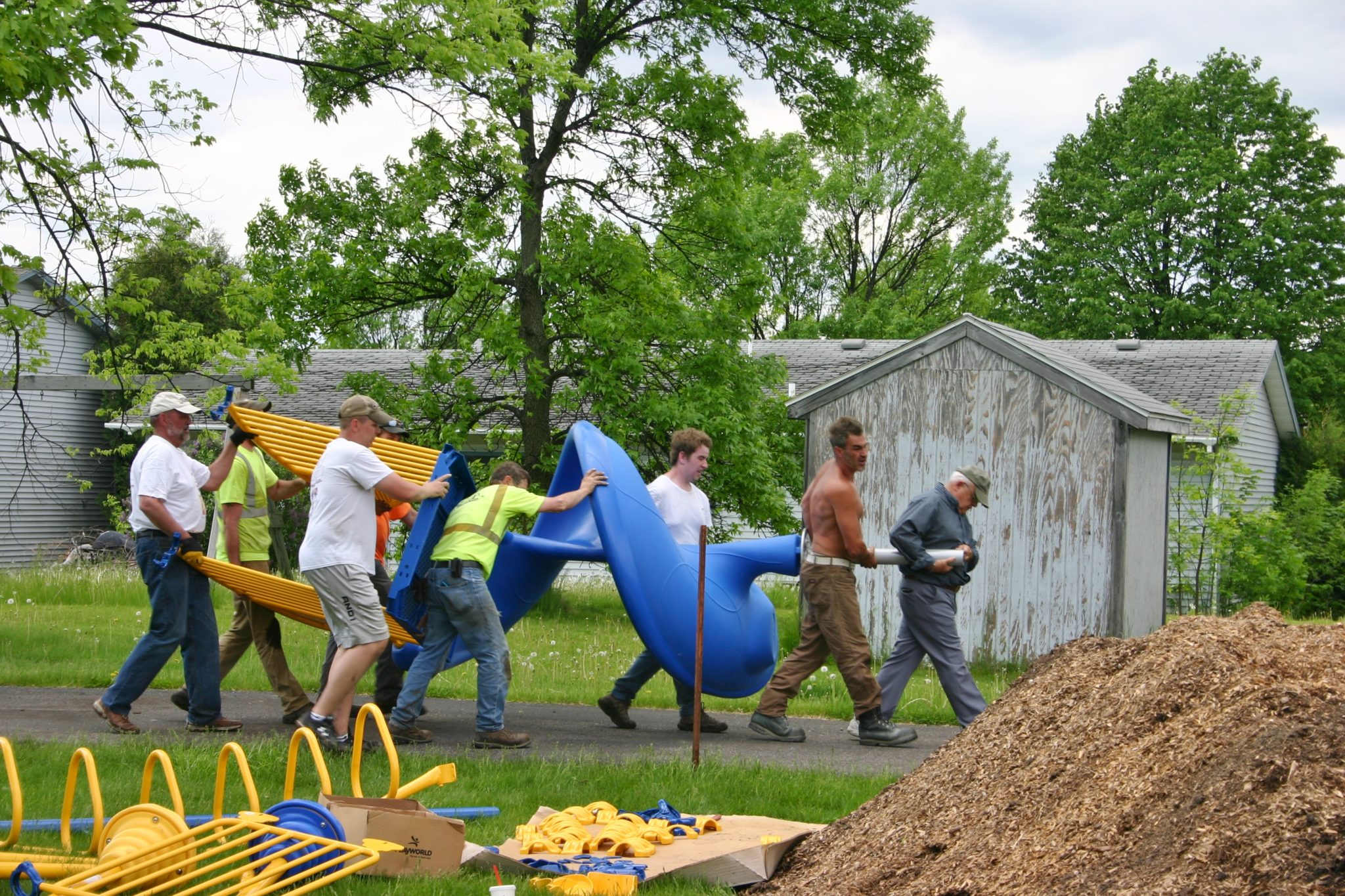 men carrying the pieces for the playground equipment