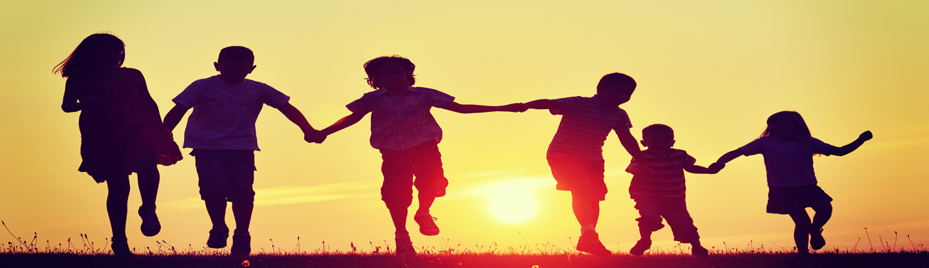 Children holding hands playing at Sunset